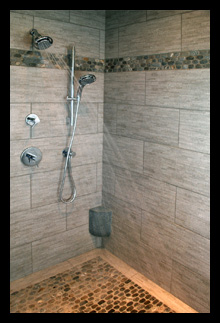 custom shower with pebble stone floor and custom foot rest for new master suite in residence